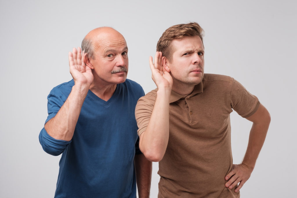 Two men hearing with hand on ear isolated on a white background. Please speak loudly.